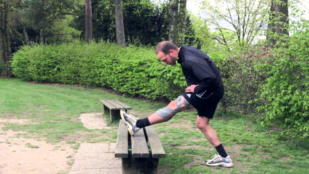 man-stretch-park-bench