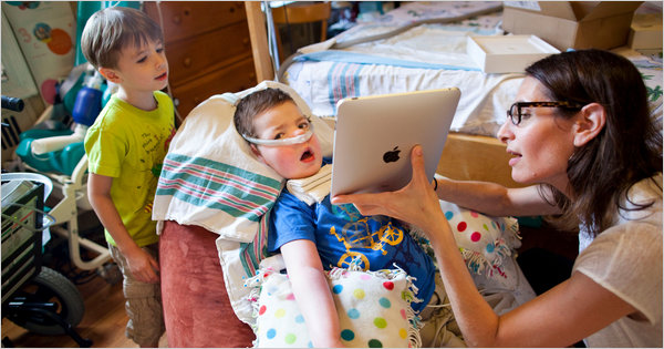FIRST TIME Owen Cain in August with his new iPad. His mother, Ellen Goldstein, and brother, Nathaniel, helped. Michael Nagle photo for The New York Times.