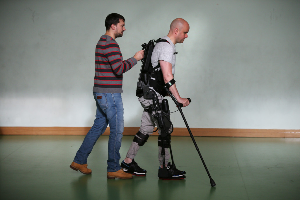 Mark Pollock is helped by his assistant as he walks using the Ekso Bionics robotic exoskeleton at Trinity College in Dublin 7th November 2015. Photo by Peter Macdiarmid for the Mark Pollock Trust.