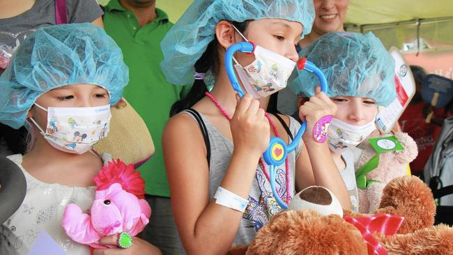 From left, Isabella Chang, 6, Nicole Chang, 9, and Rachel Tome, 5, give their teddy bears a checkup at Joe DiMaggio Children's Hospital's teddy bear clinic during Nova Southeastern University's A Day for Children event in Davie. Sun Sentinel photo by Gina Fontana.
