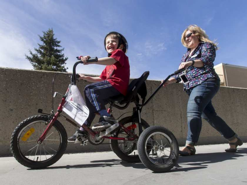 Jeremiah Botbijl, 6, rides a customized bicycle while being followed by Sheralee Stelter, executive director of Cerebral Palsy Kids and Families, on Saturday. Lyle Aspinall photo, PostMedia.