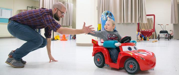 "A child tries a car. Assistant Professor Sam Logan works with a child and his family as they try a modified toy car for the first time at Oregon State University. OSU is now a site for ""Go Baby Go,"" a program that modifies toy cars for children with disabilities."