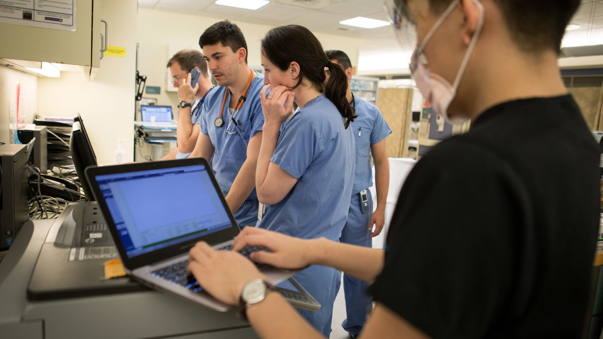 Scribe Warren Lam (right) works on notes, as attending physician Dr. Laura Burke (center) and Dr. Daniel Willner discuss a patient case, at Beth Israel Deaconess Medical Center Emergency Department on April 19, 2016, in Boston, Massachusetts. Kayana Szymczak for STAT