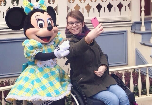 Chloe sat in a wheelchair getting a selfie with minnie mouse